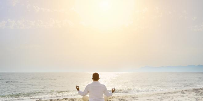 A man meditating on the beach facing a calm sea