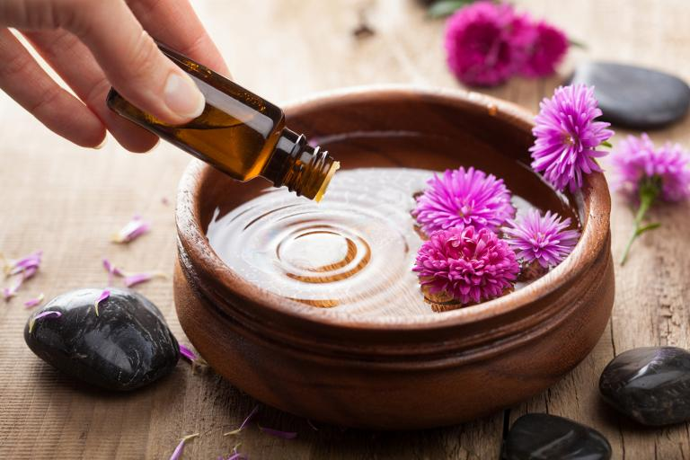 Essential oil being dripped in to a wooden dish for aromatherapy.