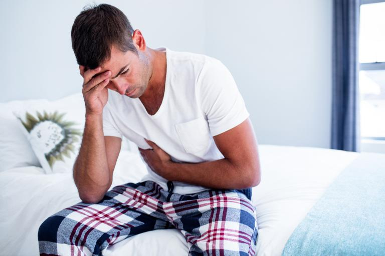 A man sitting on his bed with stomach discomfort.