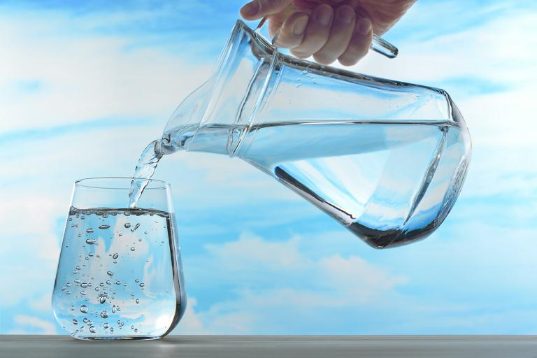 A pitcher of water pouring out into a glass.